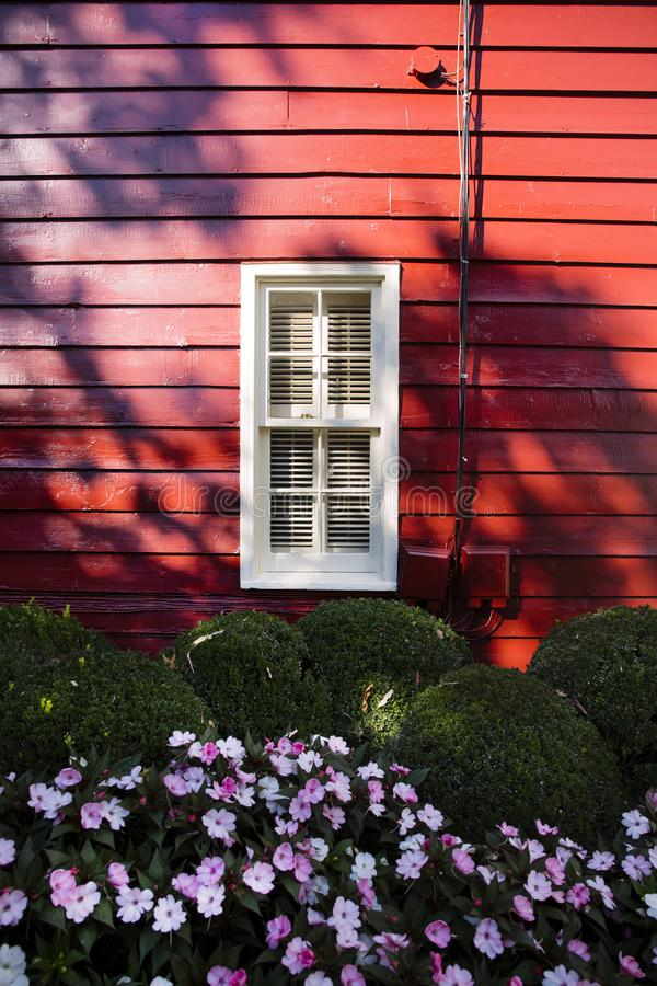 Flowers under window of historic building with red wooden wall in Washington Virginia. royalty free stock photography