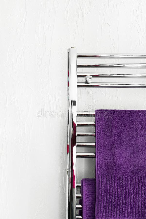 Purple fluffy terry towels hanging on stainless steel warmer rack installed in bathroom. White wall background. Interior design royalty free stock photography