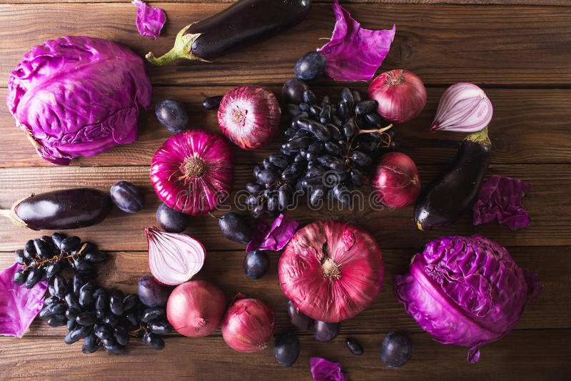 Purple fruits and vegetables. Blue onion, purple cabbage, eggplant, grapes and plums royalty free stock photography