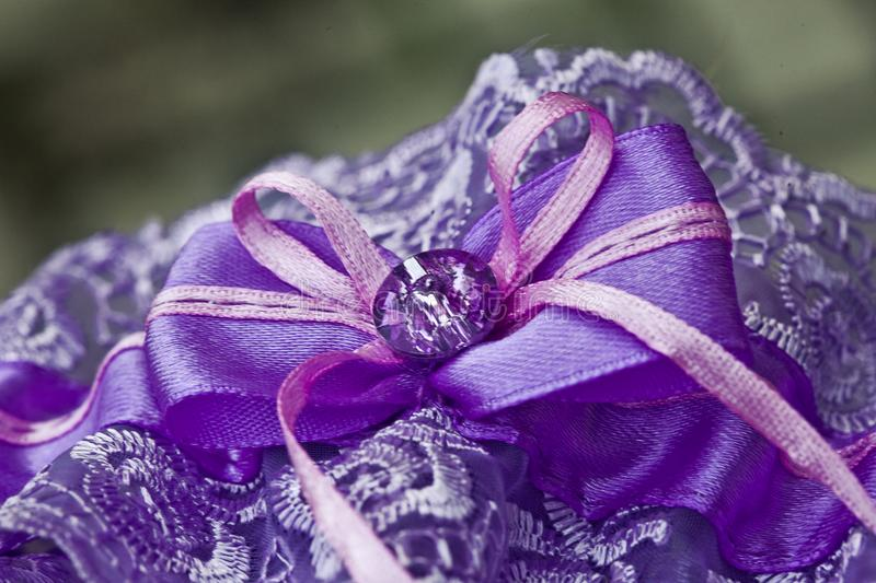 Purple garter of the bride on a blurry background, close-up stock images