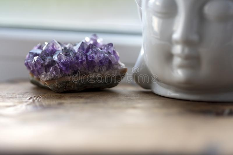 Purple and gemmy amethyst stone with White Buddha head on the windowsill background. Rough ametist crystals on home. Altar, spiritual ritual meditation place stock photos