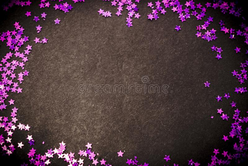 Purple glitter stars black background and copy space stock photo