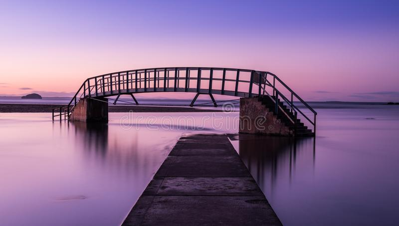 Purple glow on Bridge to Nowhere. This bridge is known as `The Bridge To Nowhere` and was built as part of Dunbar`s Victorian beach improvement scheme. It