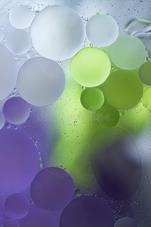 Purple, Green Gradient Oil drops in the water -abstract background.  royalty free stock photos