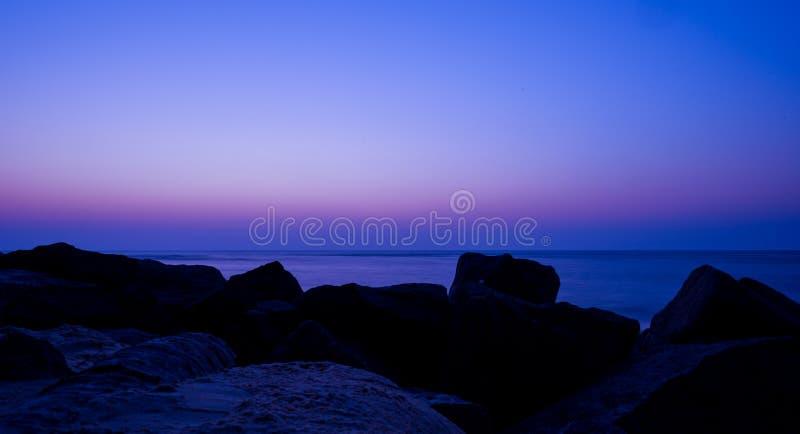 Purple haze. Blue night with purple dusk on a beach royalty free stock photos