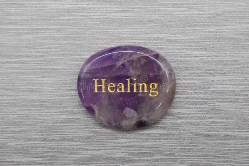 Purple Healing mood stone op grijze achtergrond stock foto