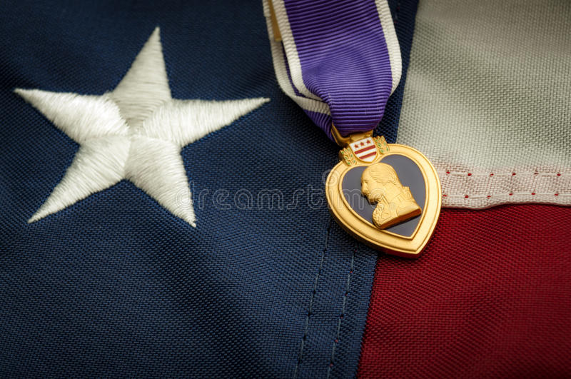 The Purple Heart medal and the American flag. The Purple Heart is a United States military decoration awarded in the name of the President to those wounded or royalty free stock photo