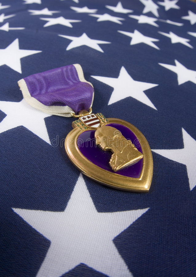 Purple Heart (memorial day series). A Purple Heart, a medal awarded to U.S. military personnel wounded or killed in action, is placed on an American flag royalty free stock photography
