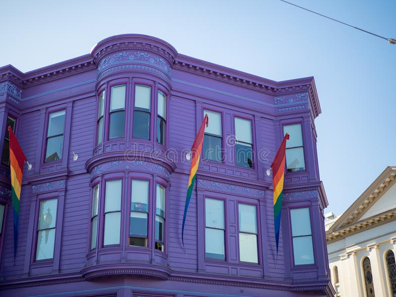 Purple house with LGBT pride rainbow flag hanging. Purple house with LGBT pride rainbow flags hanging on a sunny day royalty free stock images
