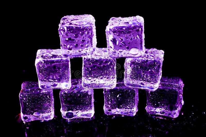 Purple ice cubes on a black table. Abstract, background, bar, beautiful, blocks, bright, bubble, clean, clear, closeup, cold, cooler, crushed, crystal, dark royalty free stock image
