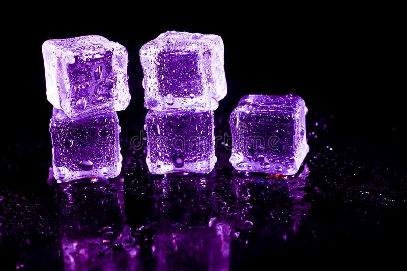 Purple ice cubes on a black table. Abstract, background, bar, beautiful, blocks, bright, bubble, clean, clear, closeup, cold, cooler, crushed, crystal, dark stock photography