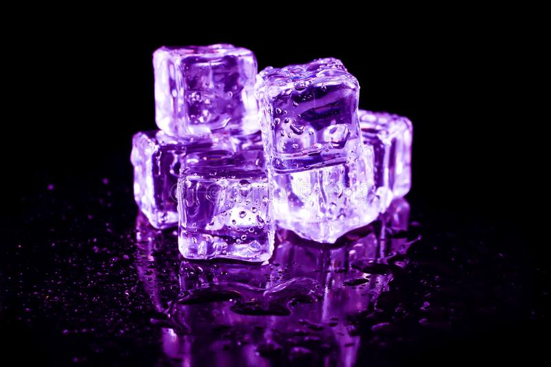 Purple ice cubes on a black table. Abstract, background, bar, beautiful, blocks, bright, bubble, clean, clear, closeup, cold, cooler, crushed, crystal, dark royalty free stock photos