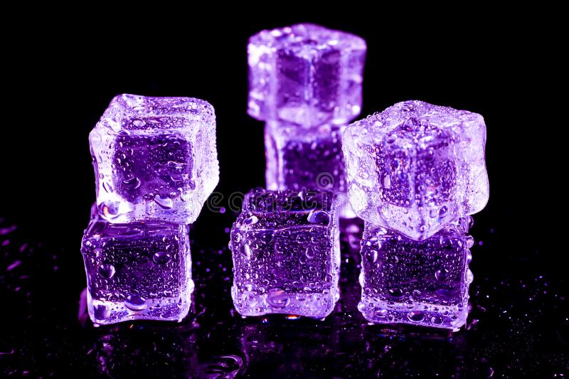 Purple ice cubes on a black table. Abstract, background, bar, beautiful, blocks, bright, bubble, clean, clear, closeup, cold, cooler, crushed, crystal, dark stock image