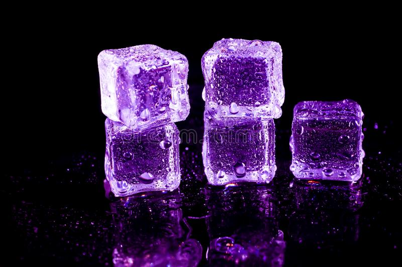 Purple ice cubes on a black table. Abstract, background, bar, beautiful, blocks, bright, bubble, clean, clear, closeup, cold, cooler, crushed, crystal, dark stock images