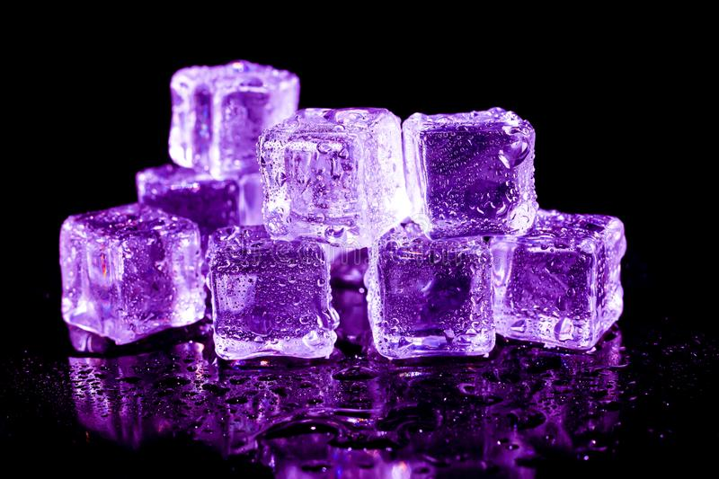 Purple ice cubes on a black table. Abstract, background, bar, beautiful, blocks, bright, bubble, clean, clear, closeup, cold, cooler, crushed, crystal, dark royalty free stock photography
