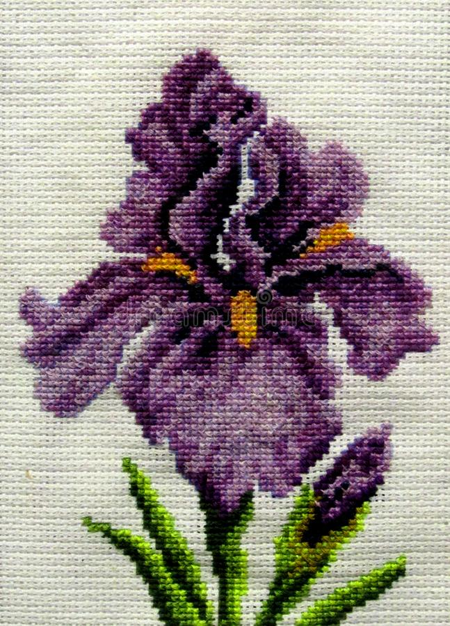 Purple iris flower with leaves embroidered with thread on fabric royalty free stock image