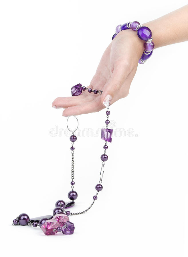 Purple jewelry and bracelet with human hand. Isolated on white stock photography