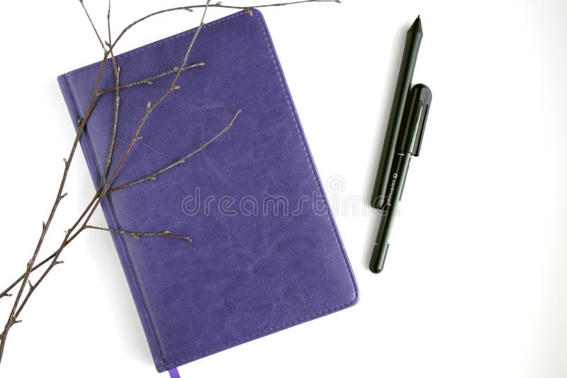 Purple Leather Notebook, Black Pen, and Brown Branches royalty free stock images