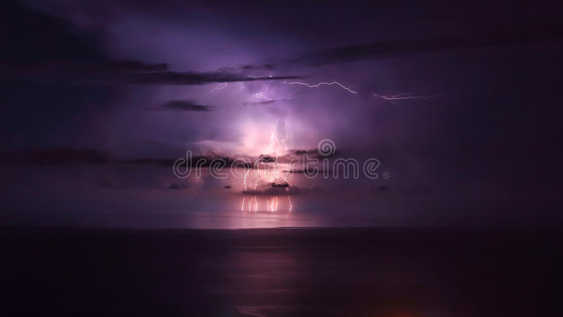 Purple lightning over the sea. Powerful thunderbolt, amazing night landscape, stormy weather in the sea, beautiful natural wallpaper stock images