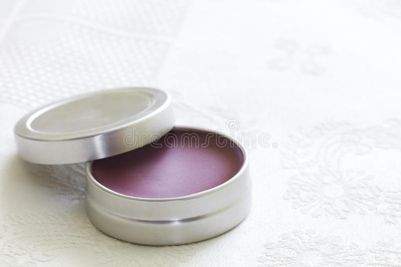 Purple lip balm with beeswax. And aroma of grosella royalty free stock photos