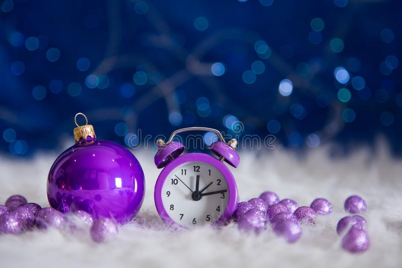 Purple little clock with Christmas ball and beads on blue bokeh. Purple little clock with Christmas ball and beads on white fur with garland lights on blue bokeh royalty free stock images