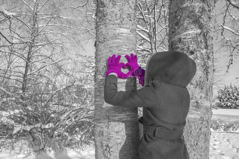 Purple love gloves. A hooded girl with purple gloves, making a heart shape with her hands against a frozen tree in the midst of winter stock photography