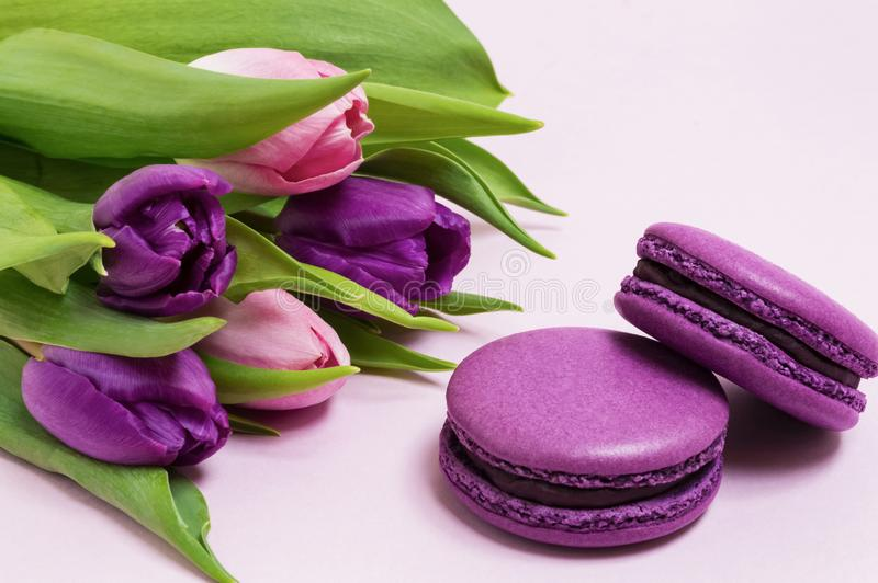 Purple macaroons, bouquet of purple and pink tulips on a light pink background. Valentines Day, 8 March, Mother`s and Women`s Day. stock images