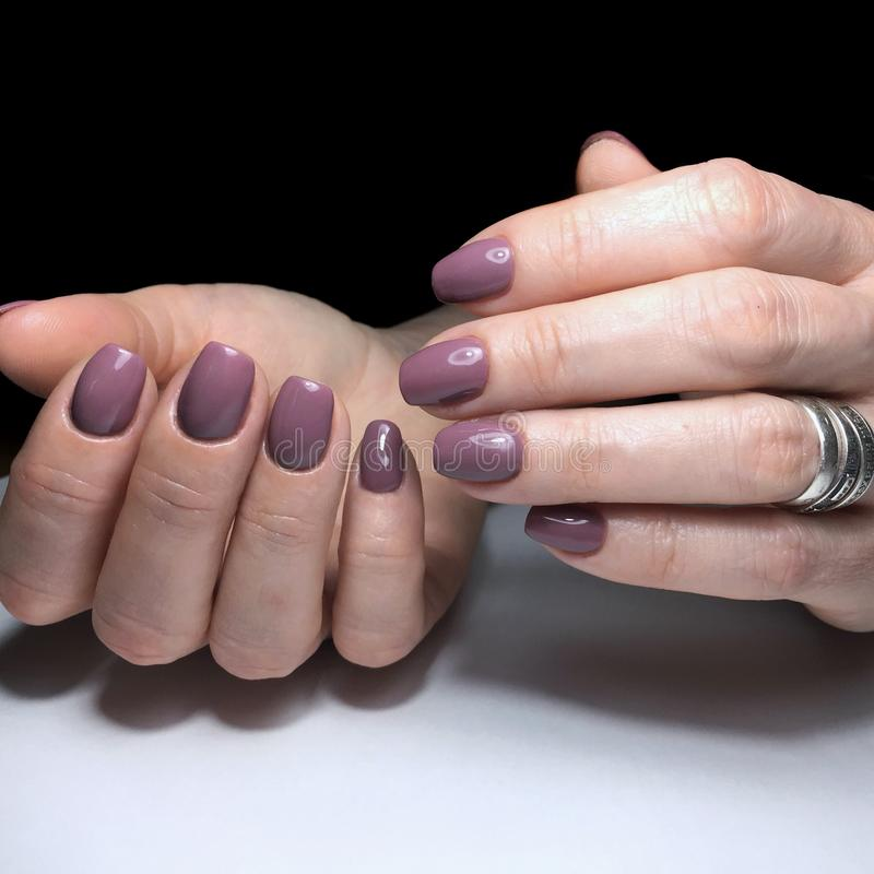 Purple manicure on the nails. Purple nail design on the fingers. Purple manicure on the nails. Purple nails design on the fingers. Manicure gel nail polish stock image