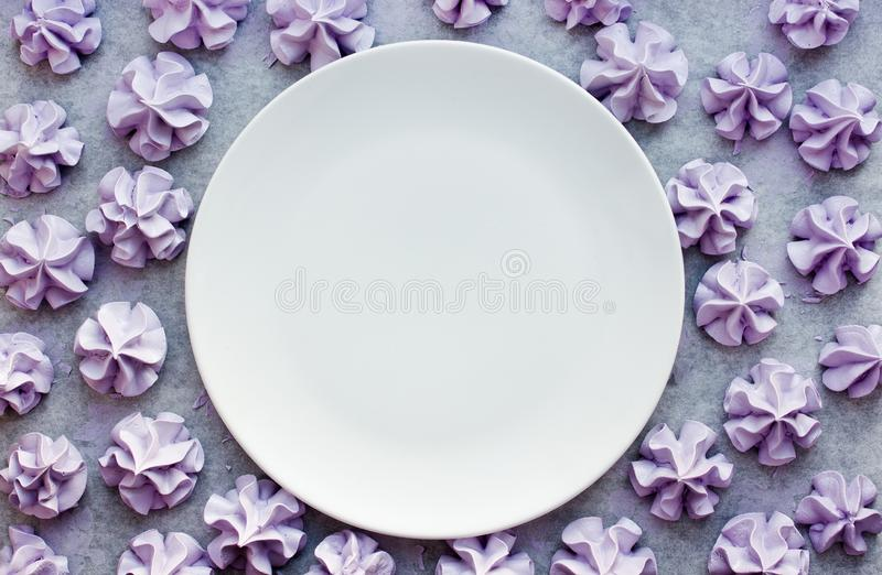 Purple meringues background and empty white plate stock photo