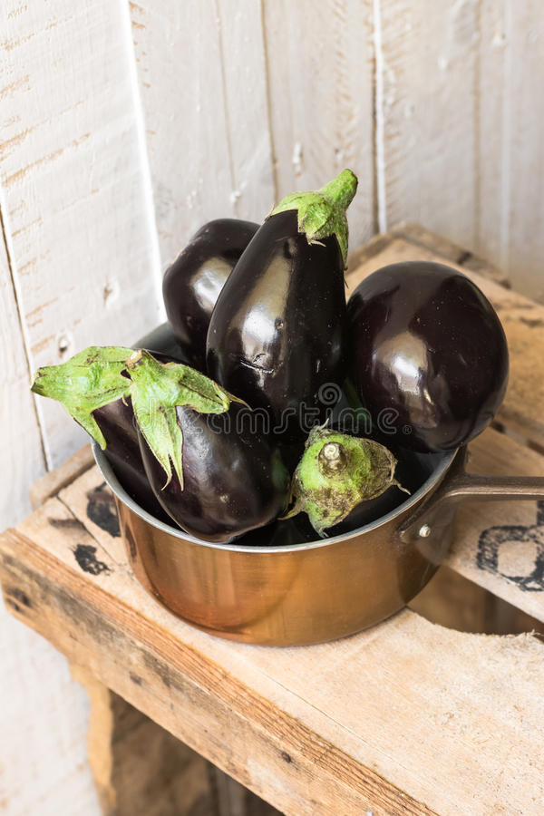 Purple mini eggplants in a copper dipper on vintage wood box on white background,summer fall, autumn harvest stock photo