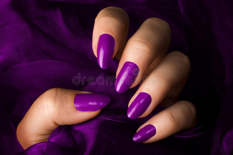 Purple nails. Female hand with purple nails is holding purple fabric stock images