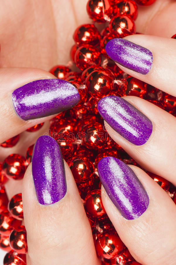 Purple nails. Female hand with purple nails holds red pearls stock image