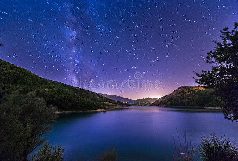 Purple night sky stars lake landscape with milky way on mountain royalty free stock photo