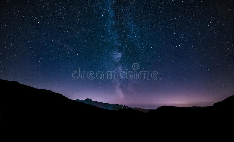 Purple night sky stars. Milky way galaxy across mountains stock photo