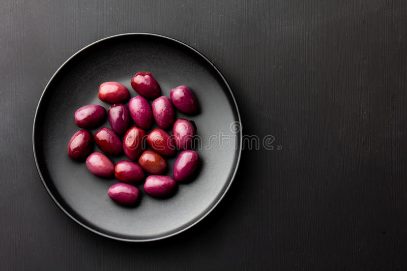 Purple olives on black plate, copy space royalty free stock image