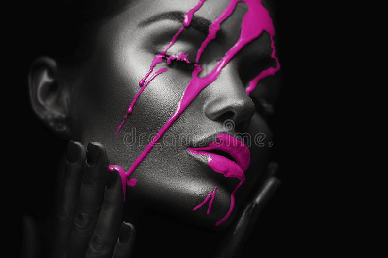 Purple paint smudges drips from woman face. liquid drops on beautiful model girl`s mouth. Sexy woman makeup. Closeup stock photography