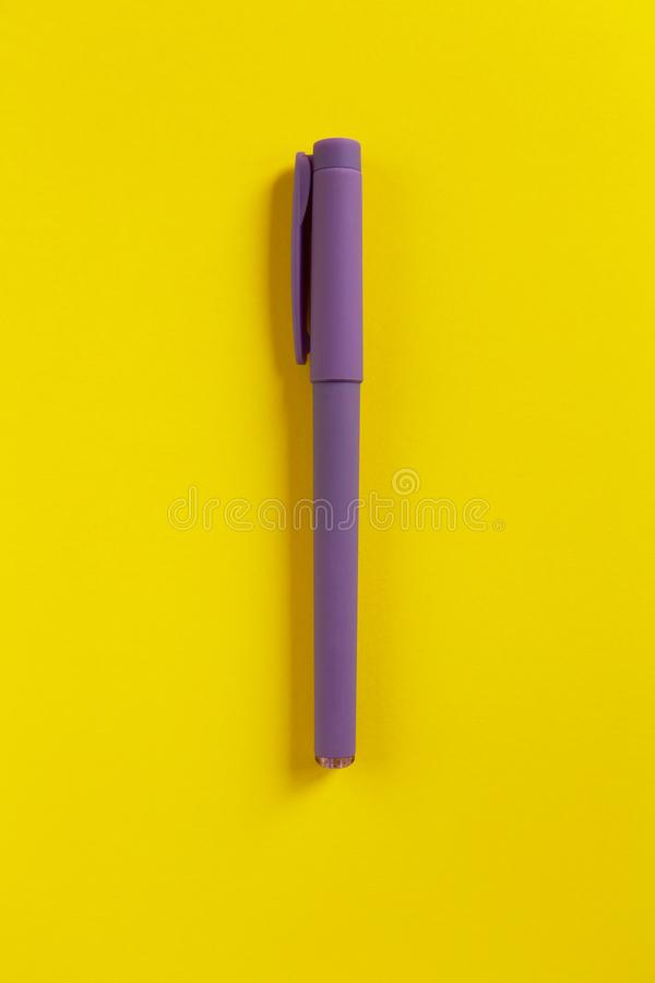 Purple pen on yellow paper background. Central composition. Back to school, education concept. Top view. Flat lay. Purple pen on yellow paper background. Central royalty free stock image