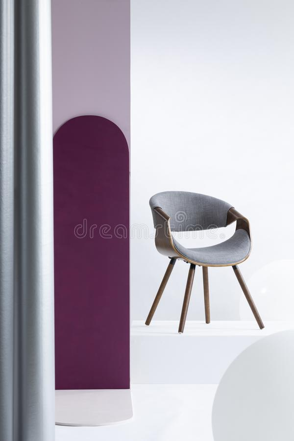 Purple pillar next to a gray chair in bright apartment. Interior with white walls. Real photo royalty free stock images