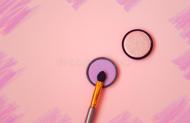 Purple and pink eyeshadows with applicator on pink background. Top view, copy space stock photography