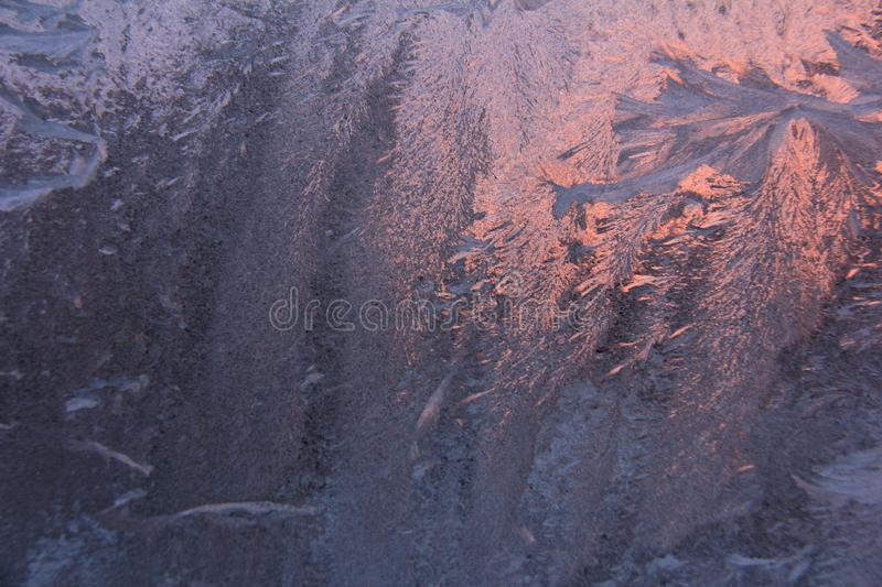 Purple-pink frosty pattern background. Texture of frost patterns. Winter frosty purple patterns on glass stock image