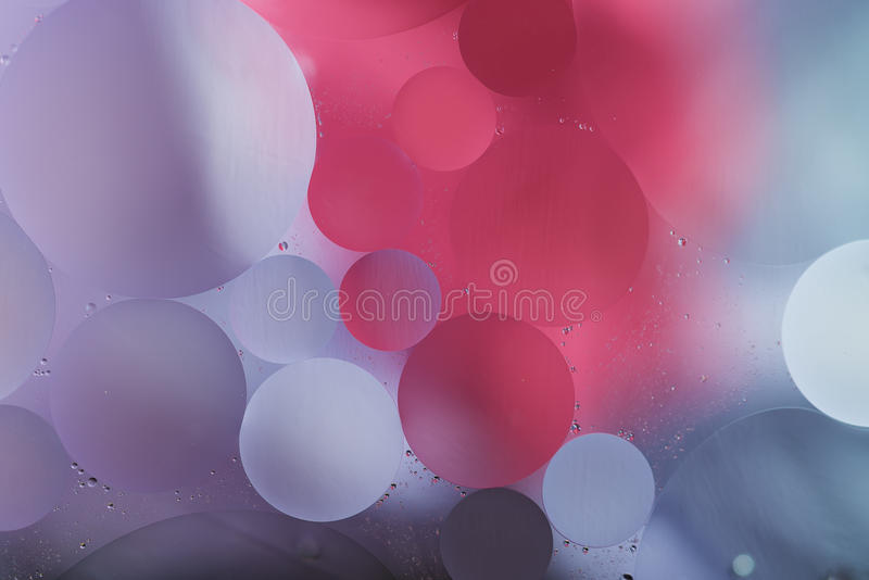Purple, pink gradient Oil drops in the water -abstract background stock photo