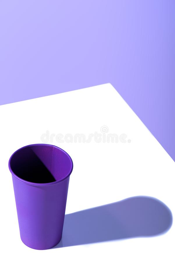 Purple plastic disposable cup, on white surface. With copy space royalty free stock photos