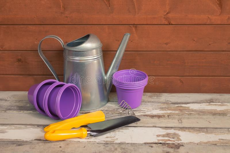 Purple plastic flower pots, watering can and yellow gardening tools on aged wooden table royalty free stock photos