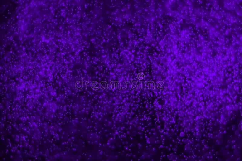 Purple plenty of flying colorful glitters bokeh texture - wonderful abstract photo background. Wonderful purple many flying vivid sparkles bokeh texture royalty free stock images