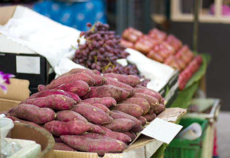 Purple potatoes on the packing case in supermarket stock photos