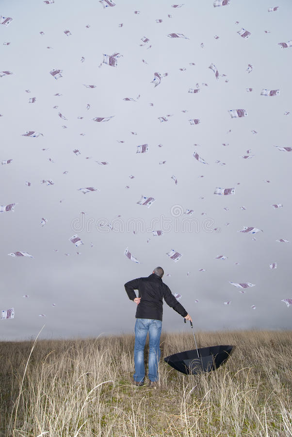 Purple rain. A man with an umbrella in the field amid a storm of money royalty free stock photos