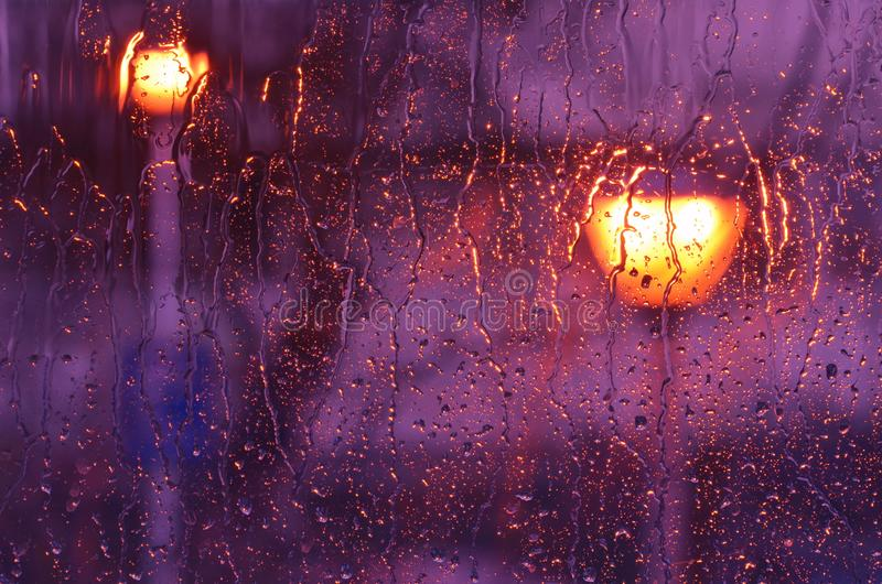 Heavy rain on window glass. Rain water drops running on window glass lit by street lamps. Blurred background, purple color