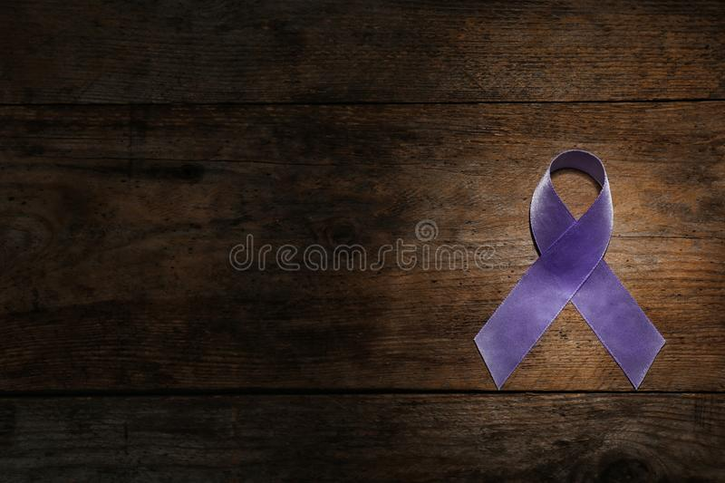 Purple ribbon on brown wooden background, top view. Domestic violence awareness. Purple ribbon on brown wooden background, top view with space for text. Domestic royalty free stock image