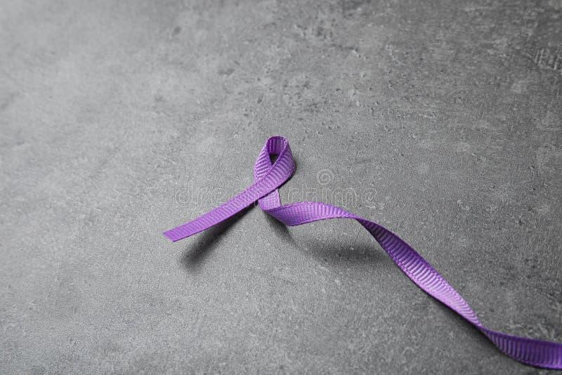 Purple ribbon on grey stone background. Domestic violence awareness. Purple ribbon on grey stone background, space for text. Domestic violence awareness stock images
