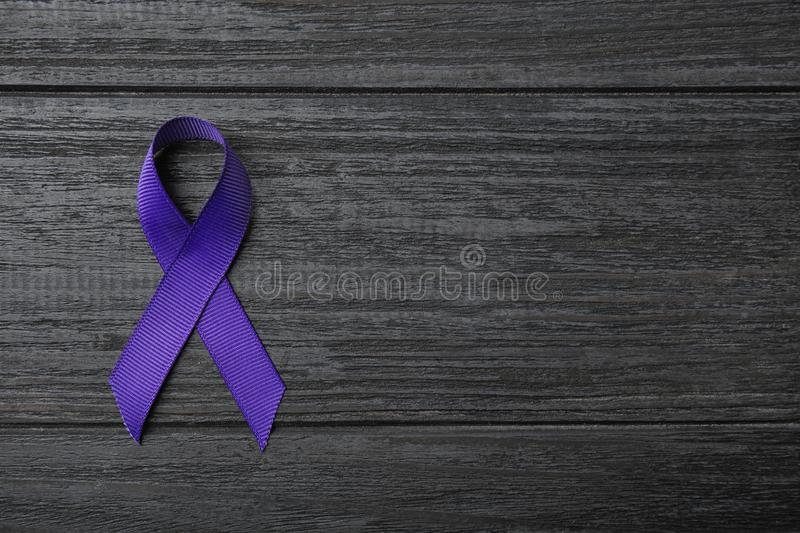 Purple ribbon on grey wooden background, top view. Domestic violence awareness. Purple ribbon on grey wooden background, top view with space for text. Domestic stock image